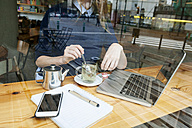 Young woman with laptop and cup of tea in a cafe, partial view - VABF01004