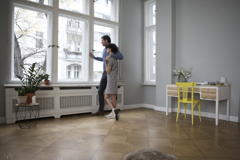 Couple looking together through window at home - RBF05430