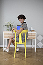 Portrait of smiling young woman sitting on yellow chair at home - RBF05433