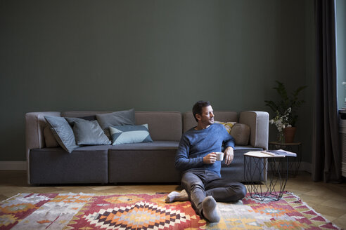 Man sitting on the floor in his living room looking through window - RBF05442