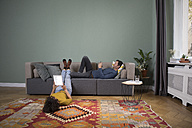 Couple relaxing together in the living room with different electronic devices - RBF05448