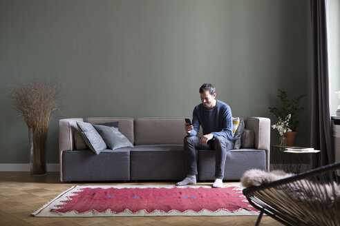 Man sitting on couch in his the living room looking at smartphone - RBF05454