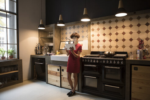 Young woman standing in the kitchen using tablet - RBF05472