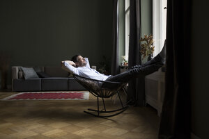 Man relaxing on rocking chair in his living room - RBF05481