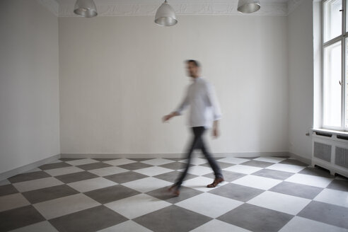 Man crossing empty room of an apartment - RBF05493