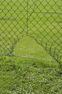 Wire mesh fence with a hole at a football ground - AXF00790