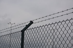 Barbed wire fence and wire mesh fence in front of grey sky - AXF00793