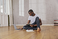 Young man sitting on floor with laptop and tablet - FMKF03394