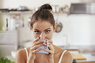 Young woman drinking coffee in kitchen - FMKF03403