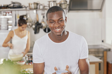 Portrait of happy young man with coffee mug in kitchen - FMKF03409