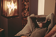 Young man with Virtual Reality Glasses lying on the couch at home - FMKF03421