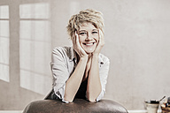 Portrait of happy blond woman with head in her hands - FMKF03445