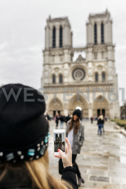 France, Paris, tourist taking picture of her friend in front of Notre Dame - MGOF02728
