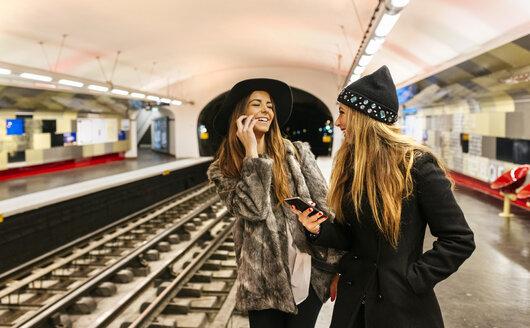 Paris, France, laughing tourists waiting at underground station platform - MGO02737
