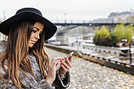 France, Paris, portrait of young woman using cell phone near River Seine - MGOF02743