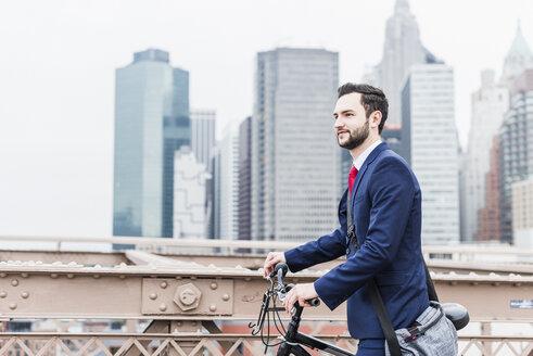 USA, New York City, businessman with bicycle on Brooklyn Bridge - UUF09634