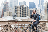 USA, New York City, laughing businessman on bicycle on Brooklyn Bridge using cell phone - UUF09640