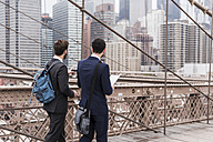 USA, New York City, two businessmen on Brooklyn Bridge - UUF09646