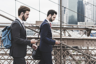 USA, New York City, two businessmen with cell phones and earbuds on Brooklyn Bridge - UUF09649