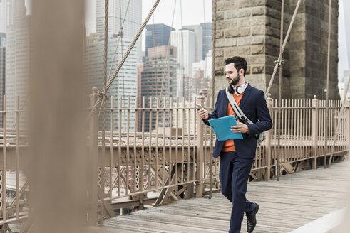 USA, New York City, man walking on Brooklyn Bridge using cell phone - UUF09661