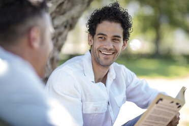 Smiling young man holding book looking at friend in park - ZEF12333