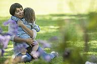 Mother hugging daughter in garden - ZEF12336