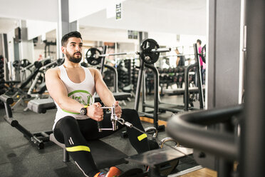 Man exercising with rowing machine in gym - JASF01434