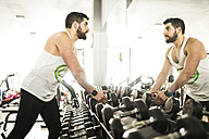 Man in gym looking in mirror - JASF01437