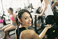 Portrait of smiling young woman lifting weights in gym - JASF01440