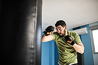 Boxer exercising with punch bag - JASF01446