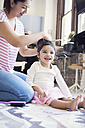 Mother doing her little daughter's hair - WESTF22427