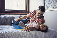 Father and daughter playing on bed - WESTF22433