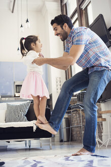 Father balancing his daughter on his foot - WESTF22436