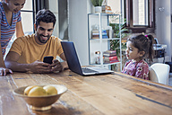 Family sitting in kitchen, parents using smart phone, daughter looking at laptop - WESTF22445