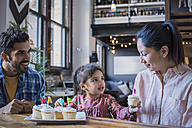 Mother and father eating birthday cup cakes with their little daughter - WESTF22451