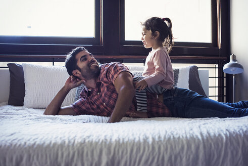 Father and daughter playing on bed - WESTF22457