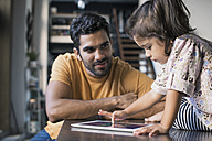 Father and daughter using digital tablet - WESTF22478