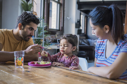 Mother and father feeding their little daughter in kitchen - WESTF22493