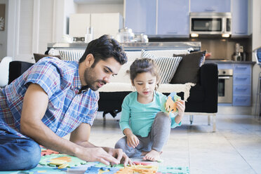 Father and daughter sitting on floor playing with children's puzzle - WESTF22496