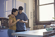 Young couple in kitchen using smart phone - WESTF22505