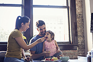 Mother and father feeding their little daughter in kitchen - WESTF22514