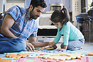 Father and daughter sitting on floor playing with children's puzzle - WESTF22520