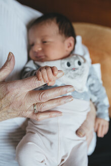 Great granddaughter holding the finger of her great grandmother, close-up - GEMF01357