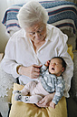 Great grandmother taking care of her great granddaughter at home - GEMF01363