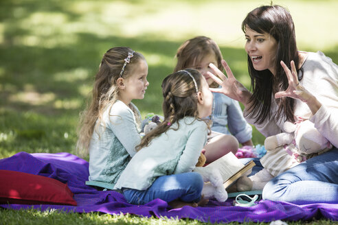 Mother telling stories to children on picnic blanket - ZEF12361