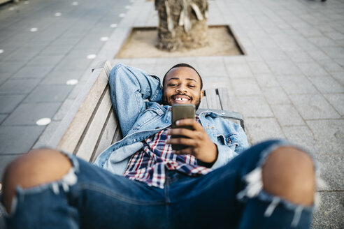 Portrait of smiling young man lying on bench looking at cell phone - JRFF01147