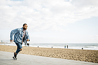 Young man running on beach promenade - JRFF01150