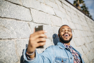 Portrait of laughing young man taking selfie with cell phone - JRFF01153