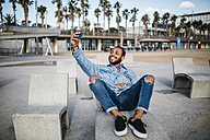 Spain, Barcelona, smiling young man taking selfie on beach promenade - JRFF01159