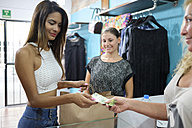 Customer paying for purchase in fashion boutique - ABAF02129